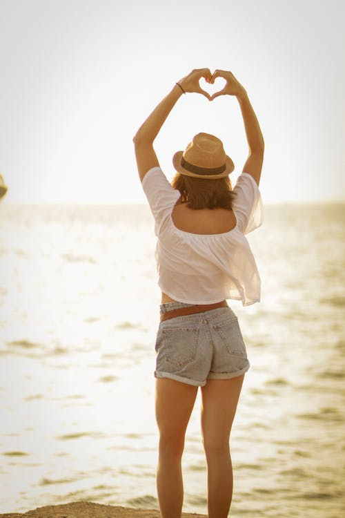Woman Standing on Beach Showing Heart Sign
