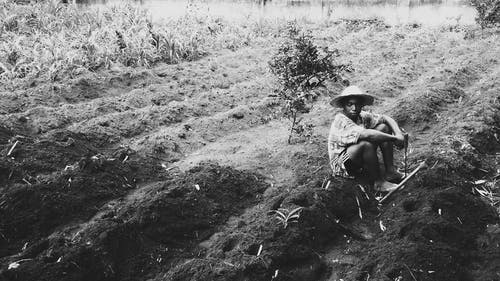 Grayscale Photography of Person Sitting on Soil