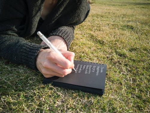 Kostnadsfri bild av anteckningsbok, bok, gräs, ord