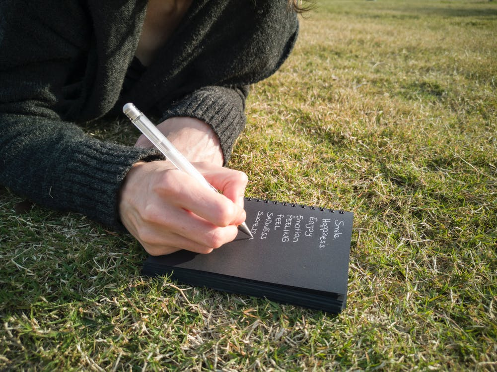 Person Writing on Book Lying Down on the Ground