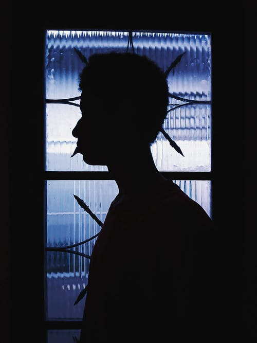 Silhouette of Boy Standing Near Light