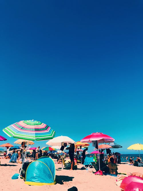 People Sitting and Standing Under Beach Parasols