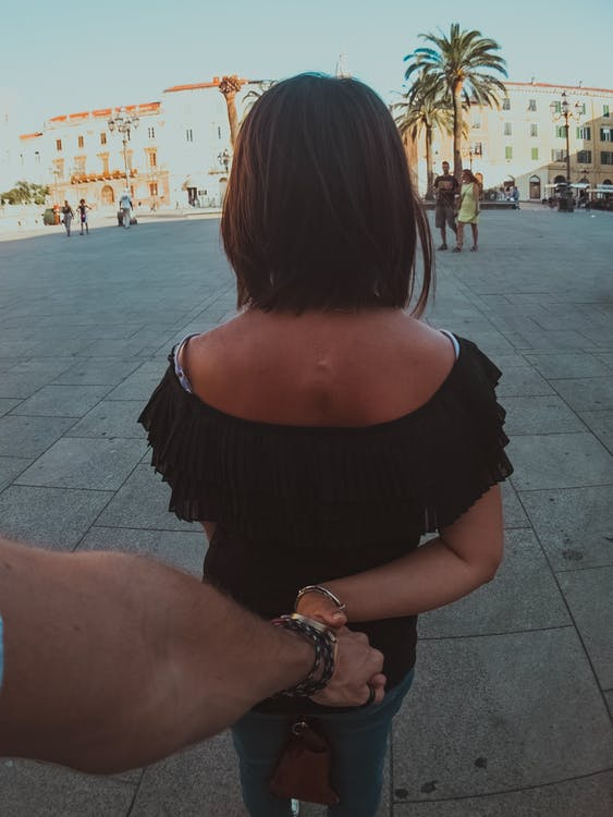 Man Holding Hand of Woman Showing Back