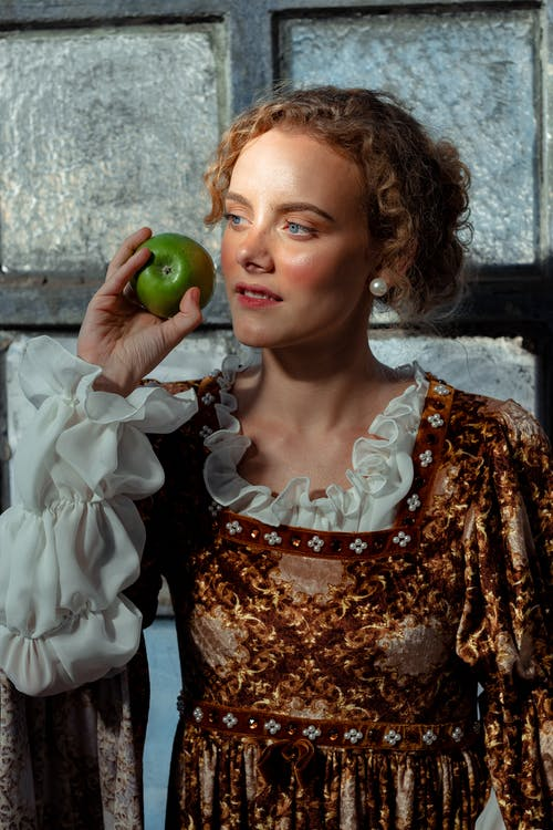 Dreamy woman in historical costume with apple near window