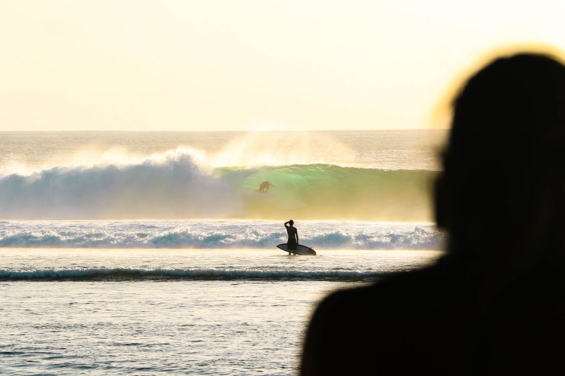 Silhouette Of Person Holding Surfboard
