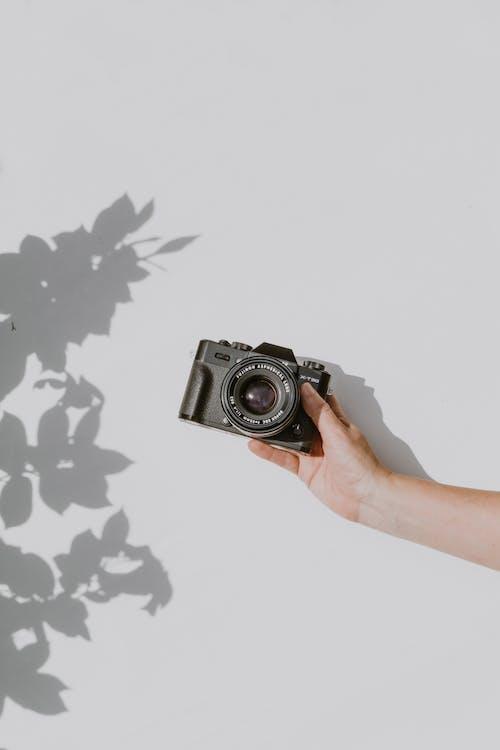 Бесплатное стоковое фото с камера, линза, рука, цифровая камера