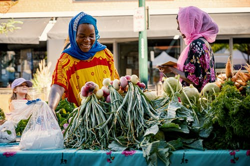 Two Women in Front of Vegetable Market