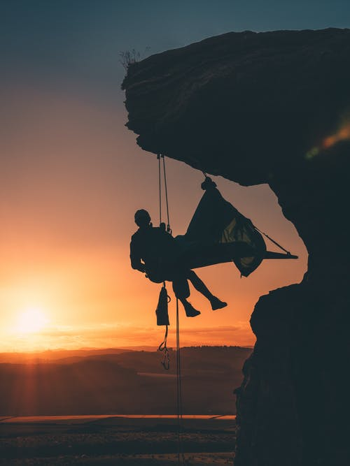Silhouette Photo of Person Hanging by the Cliff