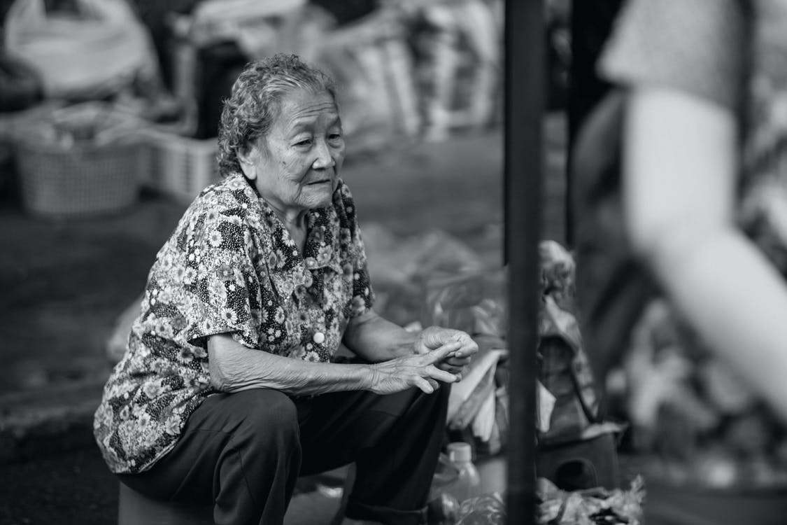 Old Woman Sitting and Touching Her Finger