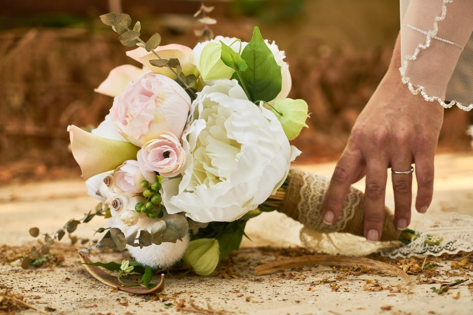 Bride picking up pink and white flower bouquet