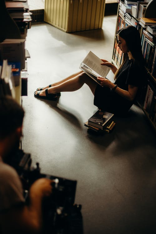 Woman Sitting On Floor Reading Book