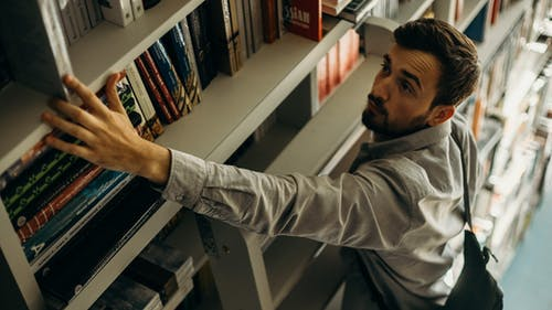 High-Angle Photo of Man Looking for a Book