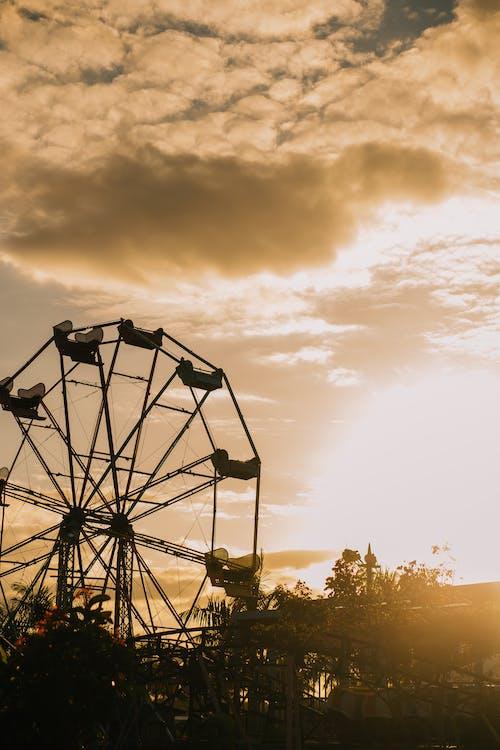Silhouette Of A Ferris Wheel Under Cloudy Sky