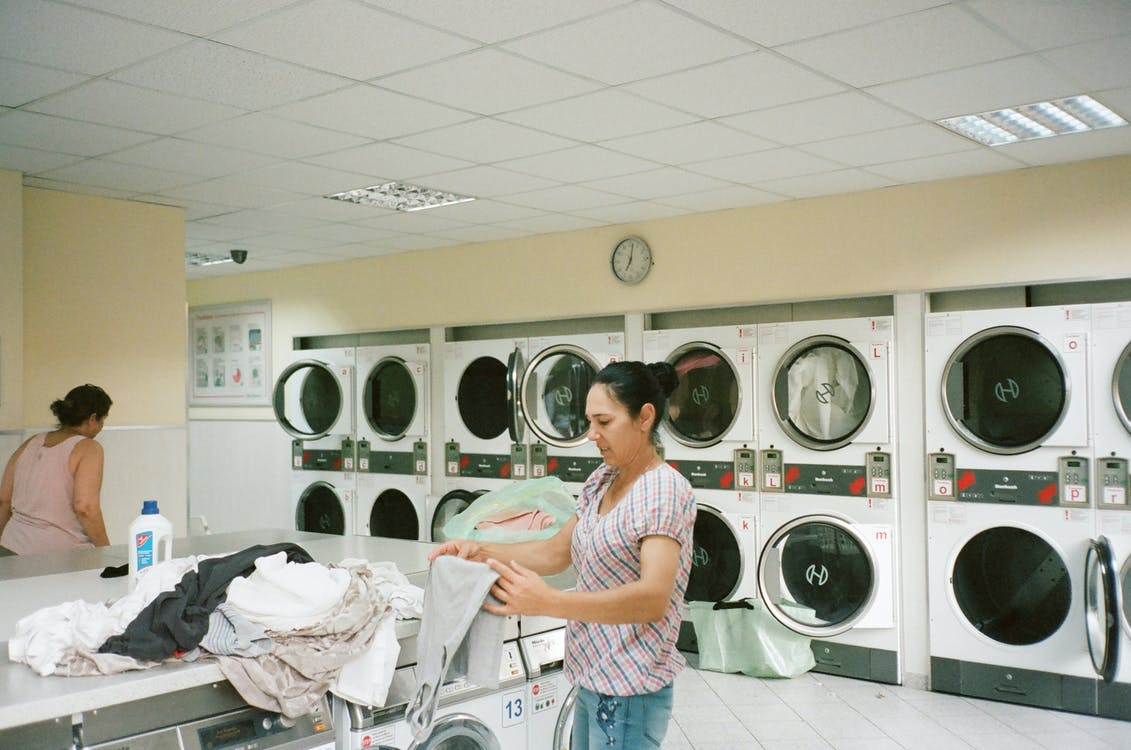 Photo of Woman Standing Inside the Laundromat