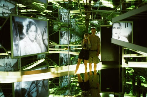 Man and Woman Standing Near Photo of Woman Inside Glass Room