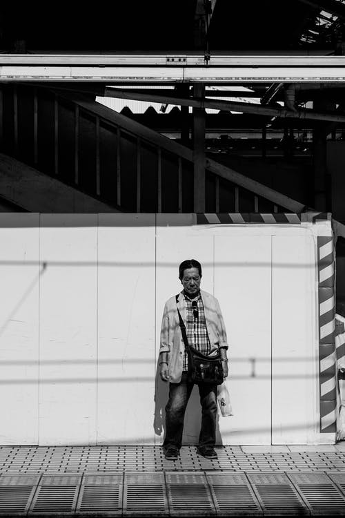Grayscale Photography Man Standing Near the Wall