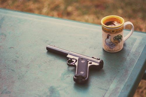 Photo of Handgun Near Mug
