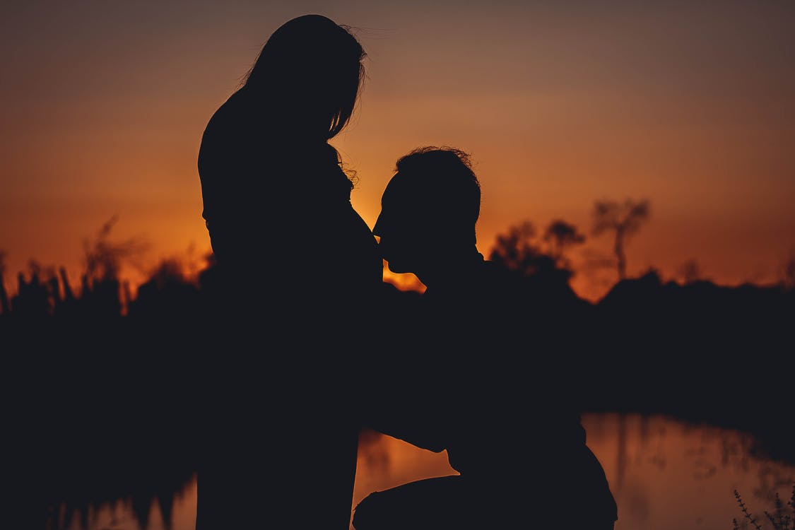 Silhouette Photo of Man Kissing His Wife Pregnant Stomach