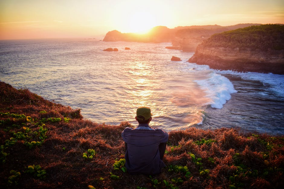 Man sitting on grass by the cliff