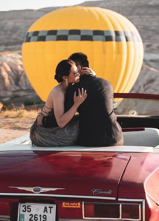 Man Hugging Woman While Sitting on Car