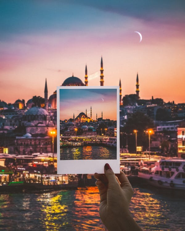Person Holding a Photo of City Buildings