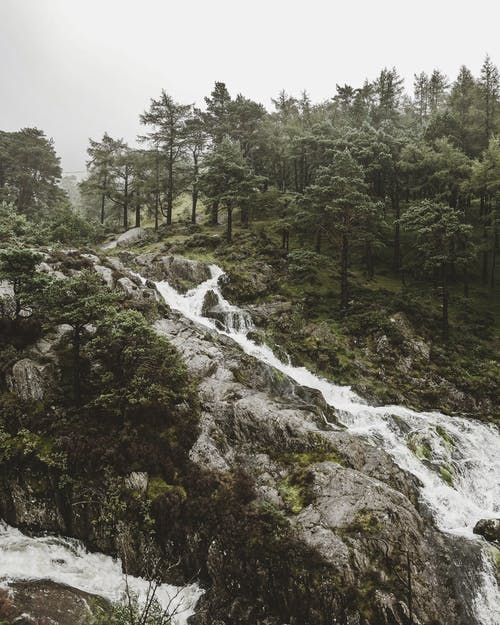 Waterfall on green hills with woods