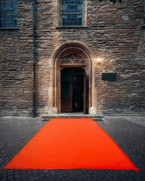 Orange Carpet Pathway Leading To The Doorway Of Brown Concrete Building With A Illuminated Wall Lamp