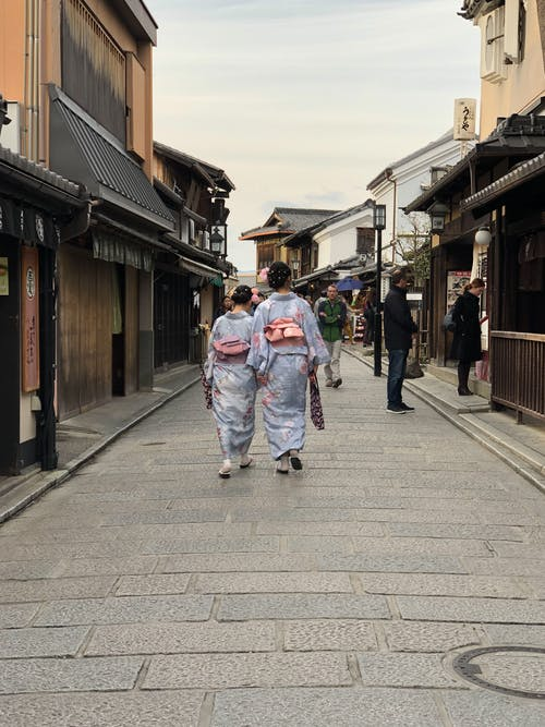 Two Women Wearing Blue Floral Hakamas Walking on Street
