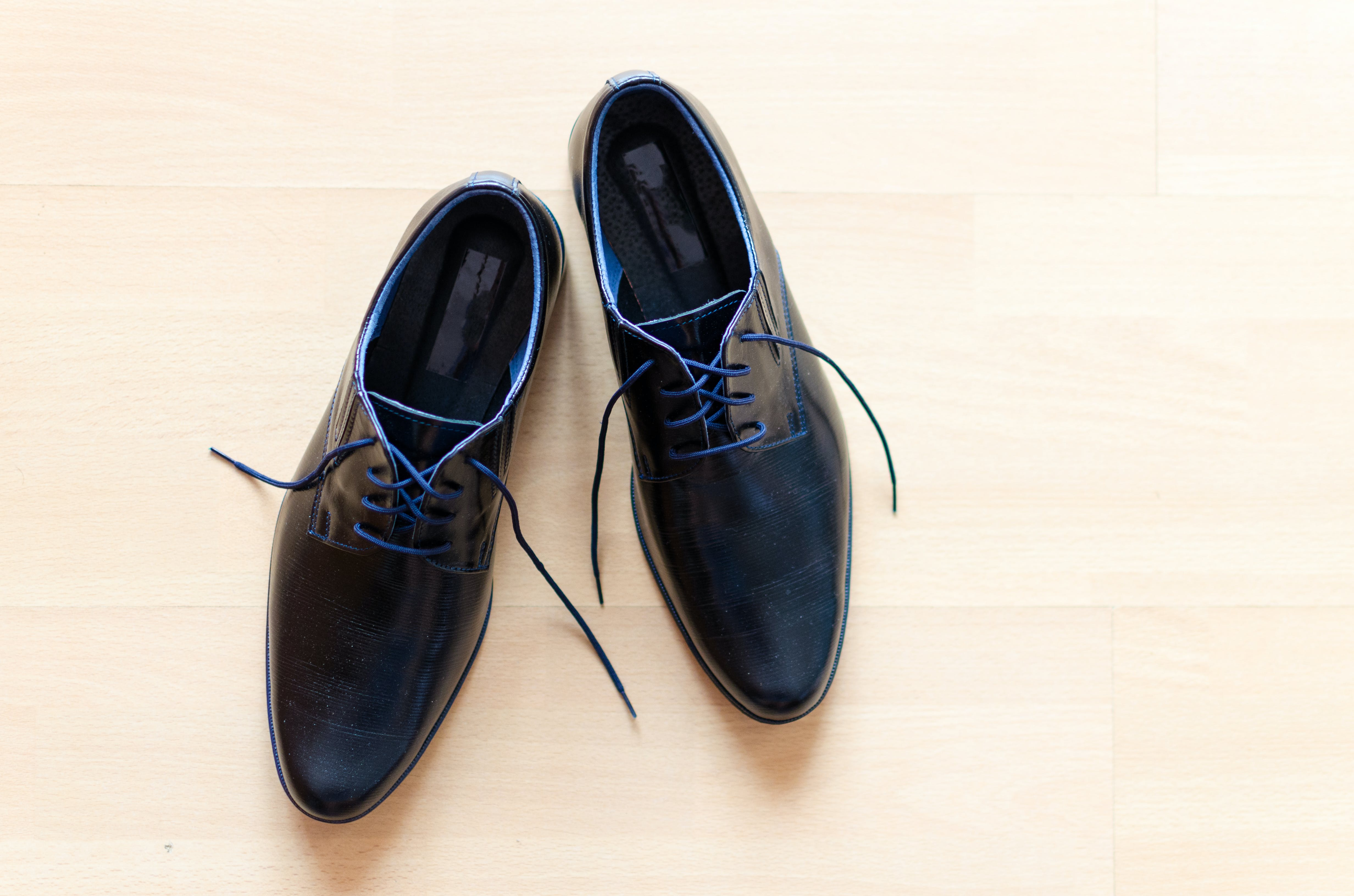 Pair of Black Leather Derby Shoes Placed on Brown Surface