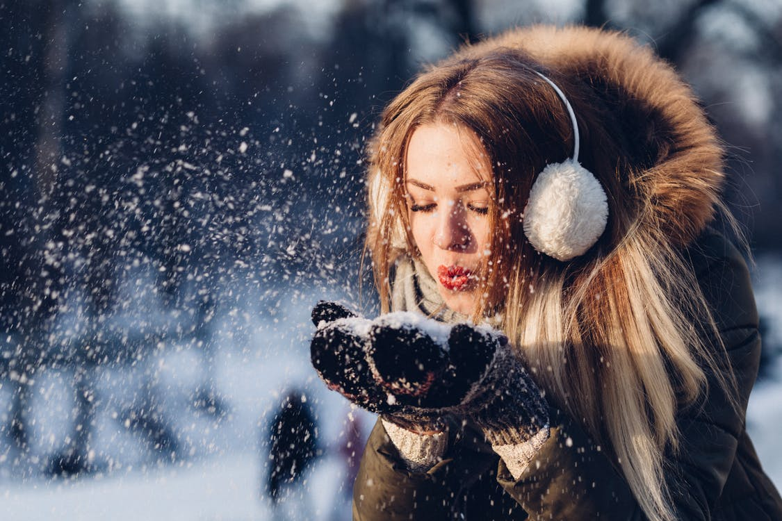 Woman Blowing Snow from Hand