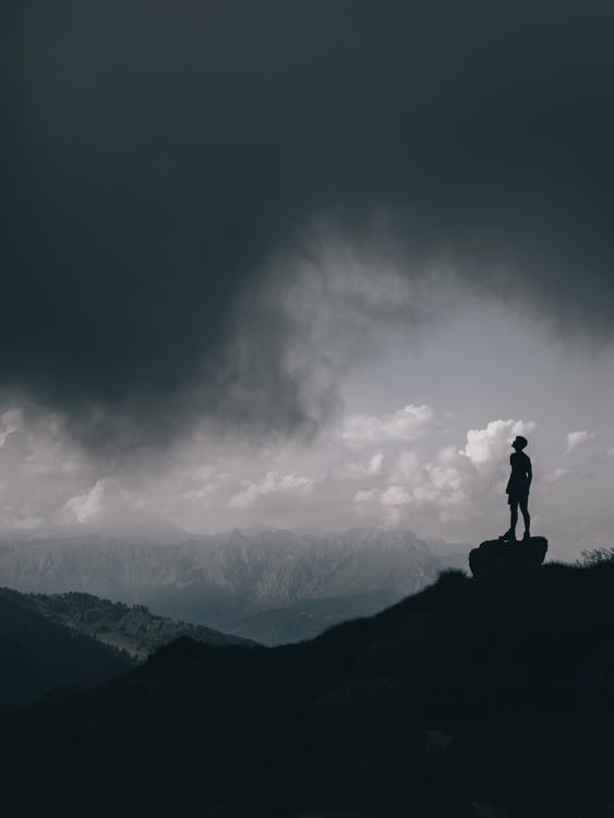 Photo Of Man Standing On Rock