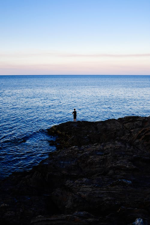 Person Standing on Rock Beside Body of Water