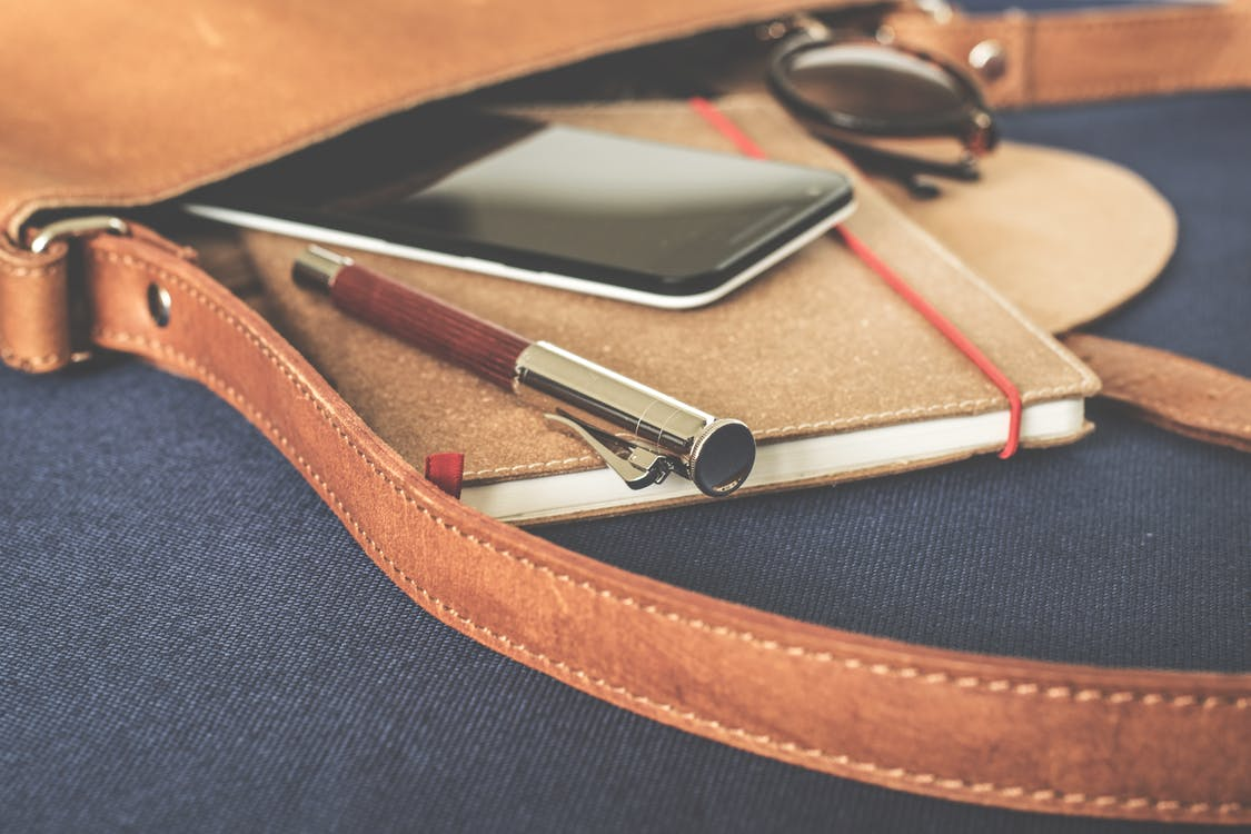 Smartphone Displaying Black Screen on Notebook Beside Pen and Sunglasses