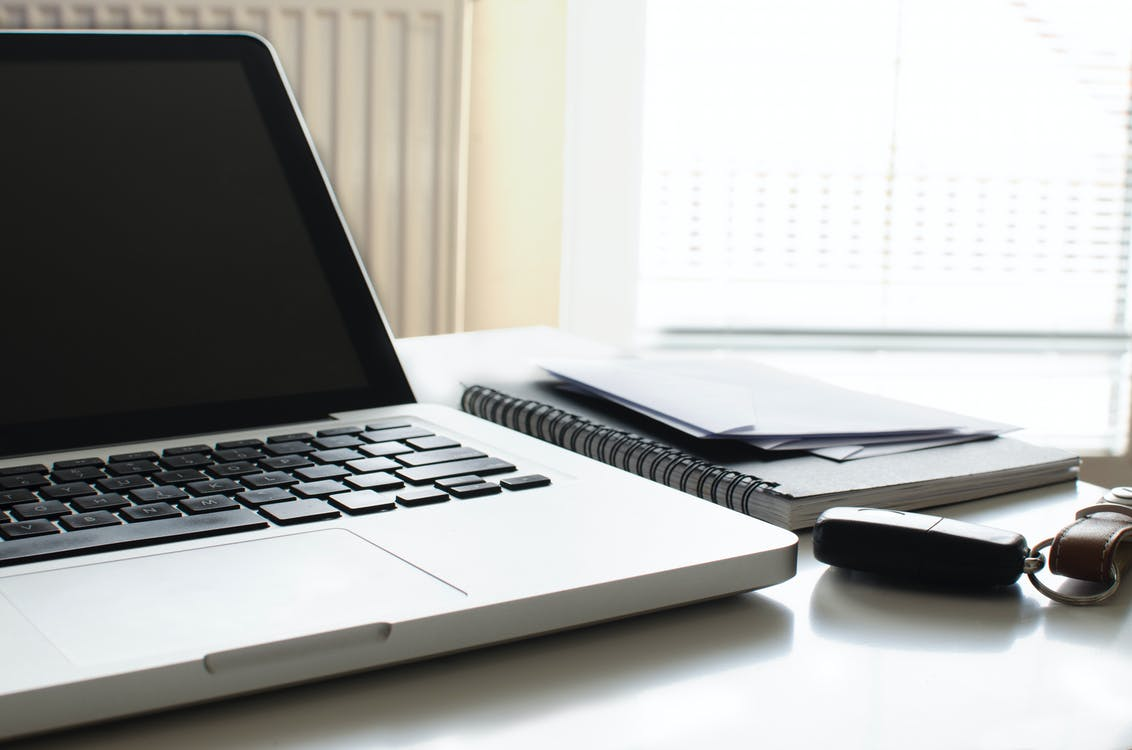 Black and Gray Laptop Computer on White Desk Beside Spiral Book