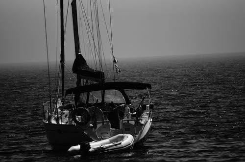 Grayscale Photography Boat on Body of Water