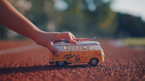 Low-Angle Photo of Person's Hand Holding a Miniature Toy Car