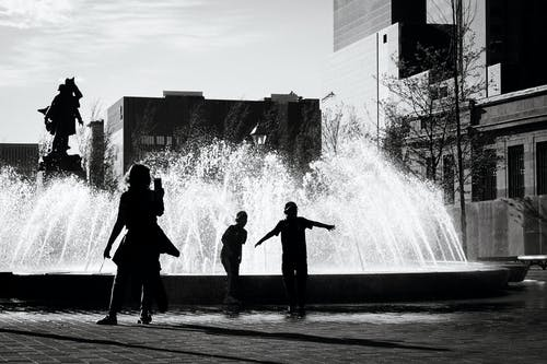 Grayscale Photography of Person Standing Beside Fountain