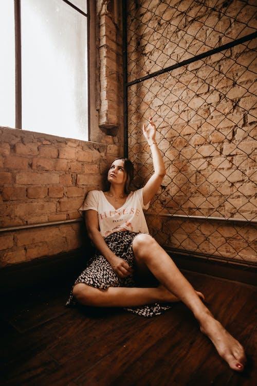 Woman Sitting on Floor Beside Glass Window