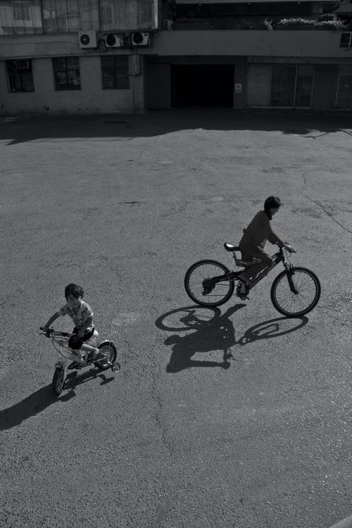 Greyscale Photo of Two Boys Riding Bicycles