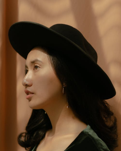 Side View Photo of Woman in Black Fedora Hat Posing Looking Away