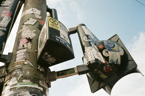 Low-Angle Photo of Stickers on a Post