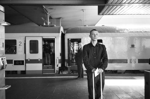 Monochrome Photo Of Man Standing Beside Train