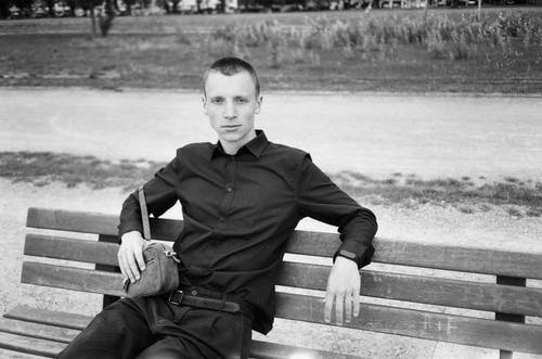Monochrome Photo Of Man Sitting On Wooden Bench