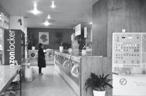 Woman in Black Coat Standing Beside Washer Dryers