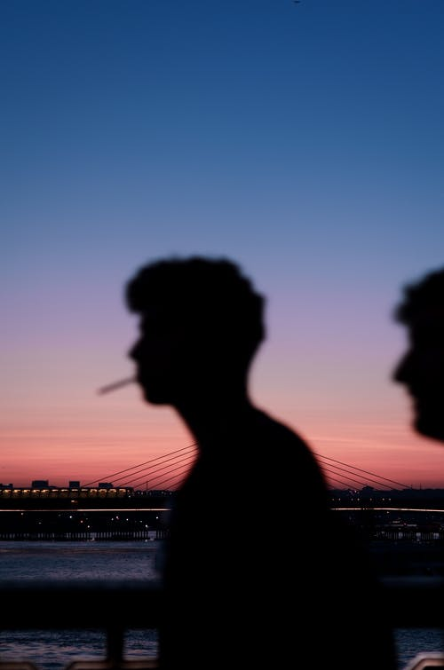 Silhouette Photography of A Man With A Cigarette On His Mouth