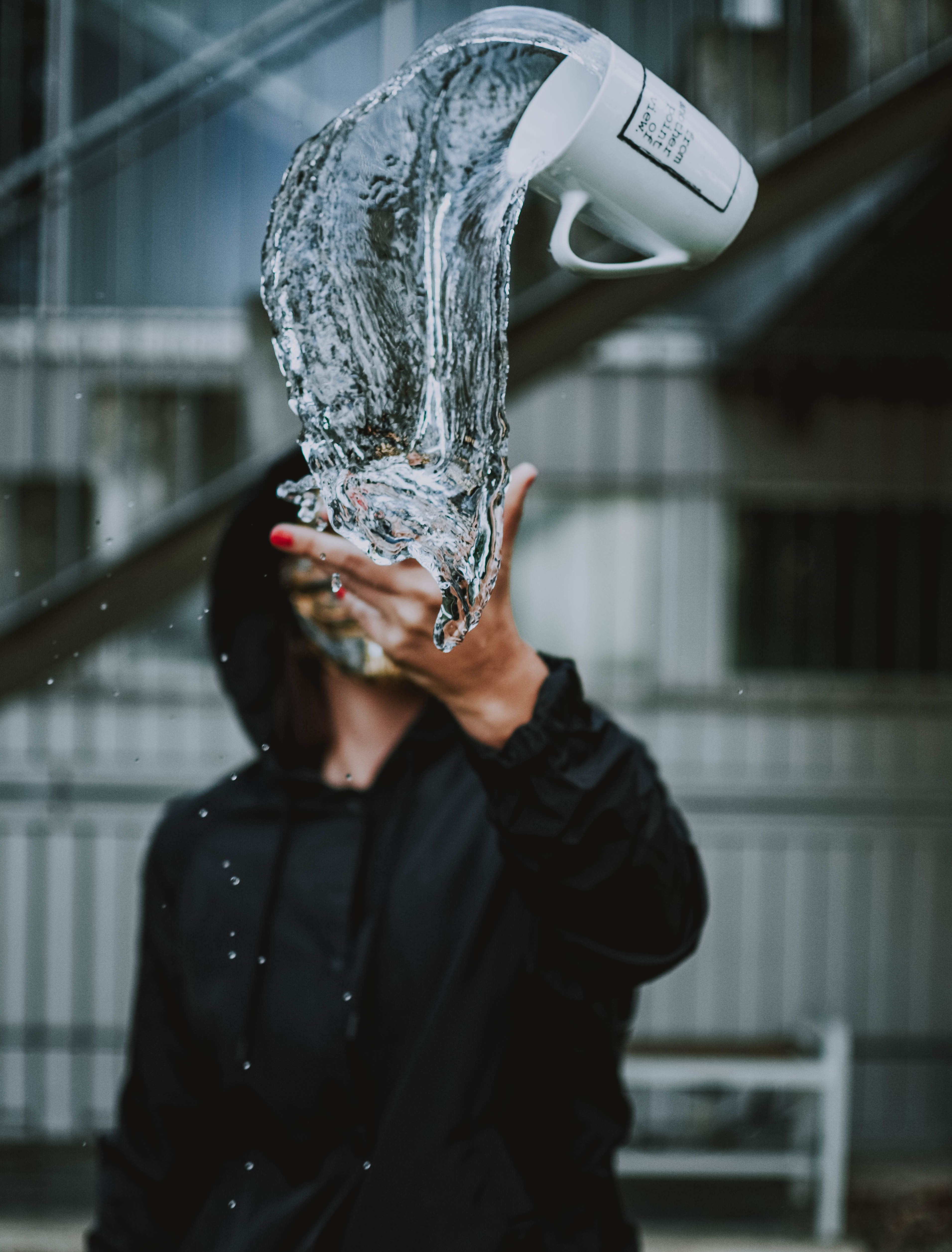 Mug in Mid Air Pouring Clear Liquid on Man's Hand