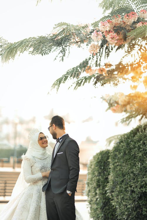 Selective Focus Photography of Woman Wearing White Abaya Wedding Dress Smiling in Front of Man in Black Tuxedo