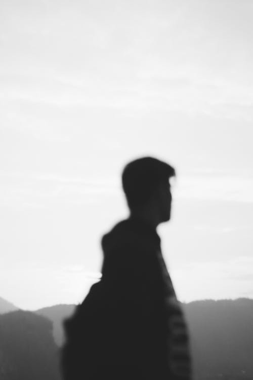 Silhouette of unrecognizable male tourist admiring mountains