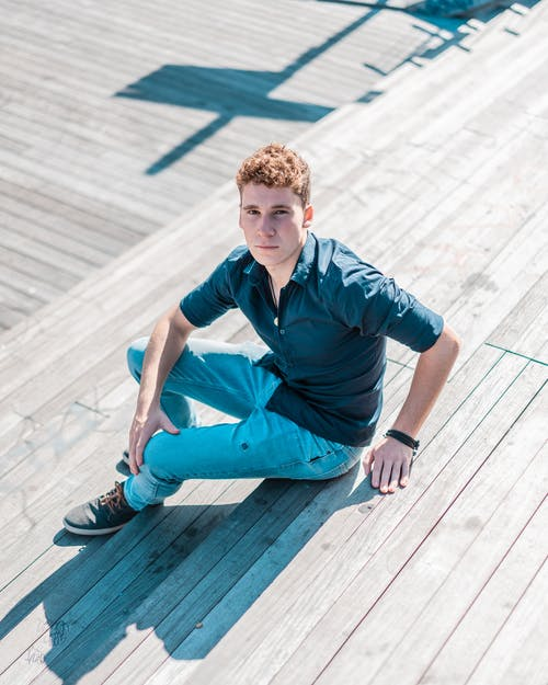 Man in Blue Collared Shirt and Blue Trousers Sitting Down on Wooden stairs