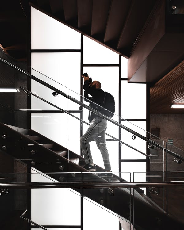 Man Standing on Stairs Holding Camera